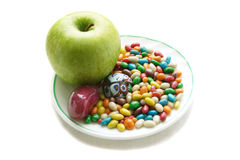 Green apple and colorful sweets on the white plate Stock Images
