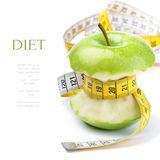 Green apple core and measuring tape Stock Images