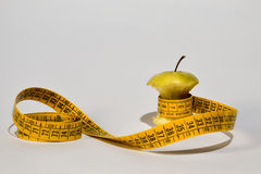 Green apple core and measuring tape Stock Photos