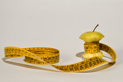 Green apple core and measuring tape Royalty Free Stock Photo