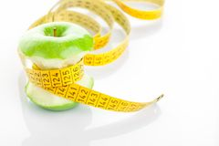 Green apple core and measuring tape Royalty Free Stock Images
