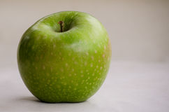 Green apple. On cream background lightsource on right Royalty Free Stock Image