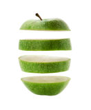 Green apple cut into slices isolated over a white Royalty Free Stock Photos