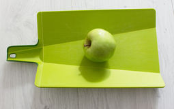 Green apple on a cutting board. And wood background Stock Image