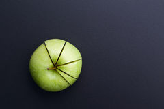 Green apple cutting in the shape of pie chart on back board. Green apple cutting in the shape of pie chart on back board Royalty Free Stock Images
