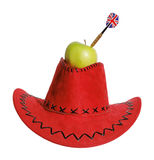 Green apple with a dart in a red hat Royalty Free Stock Photos
