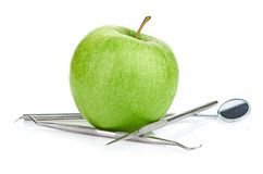 Green apple and dental tools isolated on white Stock Photo