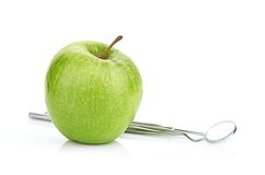 Green apple and dental tools isolated on white Royalty Free Stock Photography