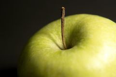 Green apple detail. Detail of a fresh green apple in black back Royalty Free Stock Photos
