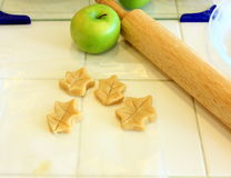 Green Apple and dough leaves for a pie. Dough decorations being prepared for baking Royalty Free Stock Image