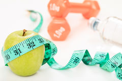 Green apple, dumbbells and measuring tape Royalty Free Stock Photo
