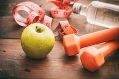 Green apple, dumbbells and measuring tape Royalty Free Stock Image