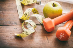 Green apple, dumbbells and measuring tape Stock Image