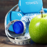Green apple, dumbbells, water and measuring tape. Health and die Stock Photo