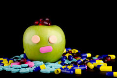 GREEN APPLE WITH EYES AND NOSE WITH MEDICINE. A green apple with eyes and nose with medicine on the ground on black background stock photography