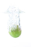 Green apple falling in water against white background royalty free stock photography