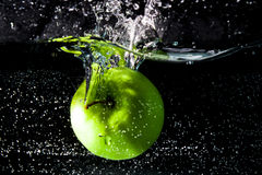 Green apple falls in to water Royalty Free Stock Images
