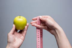 Green apple in female hands on gray background. Weight loss, diet Stock Images