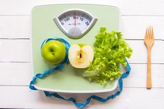 Green apple, fresh vegetable with weight scale and measuring tape for the healthy diet slimming. Diet and Healthy Concept royalty free stock photos