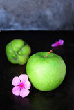 Green Apple Fruit Next to Purple Petaled Flower and Green Round Fruit on Black Table Stock Photos