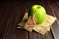 Green apple gift with thank you lable on dark wooden table background. Teachers day