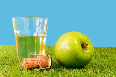 A green apple with a glass of cider Royalty Free Stock Photography