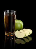 Green apple, glass of juice and three parts of an apple Royalty Free Stock Images