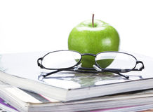 Green apple and glasses on magazine and  book stack close up Stock Photo