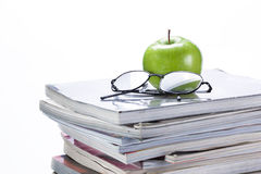 Green apple and glasses on magazine and  book stack Stock Photos
