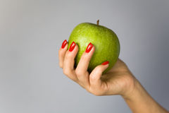 A green apple in a graceful female hand. Stock Photography