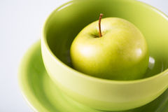 Green apple in green bowl Royalty Free Stock Photos