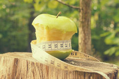 A green apple with a green ribbon and a measuring tape. Stock Images