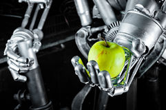 Green apple in the hands of a robot Stock Image