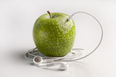 Green apple with headphones listening to music mp3 Stock Image