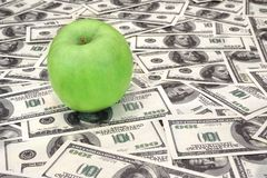 Green apple on heap of dollars Royalty Free Stock Photos