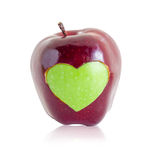 Green apple heart shape in red apple. Stock Images