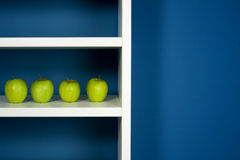 Green apple inside white bookcase Royalty Free Stock Photo