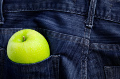 Green apple with jeans background Royalty Free Stock Photo