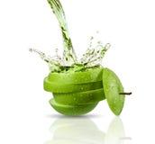 Green apple juice splashing with its fruits Stock Image