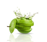 Green apple juice splashing with its fruits Stock Images