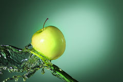 Green apple in juice stream Royalty Free Stock Photo