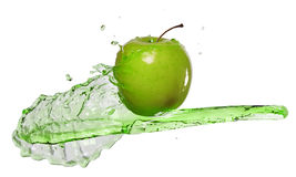 Green apple in juice stream stock photos