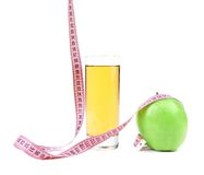 Green apple with juice and tape measure Stock Photography