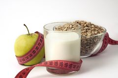 Green Apple, Kefir and Oatmeal with Measuring tape on white background royalty free stock image