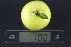 Green apple on kitchen scale Stock Image