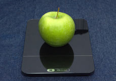 Green apple on kitchen scales closeup royalty free stock photography