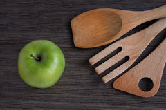 Green apple and kitchen wooden shovels Stock Photo