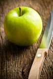 Green apple with knife Stock Photos