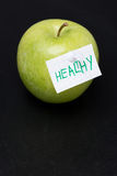 Green apple with label on a dark background Royalty Free Stock Images