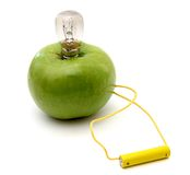 Green apple with a lamp connected to a battery Stock Image